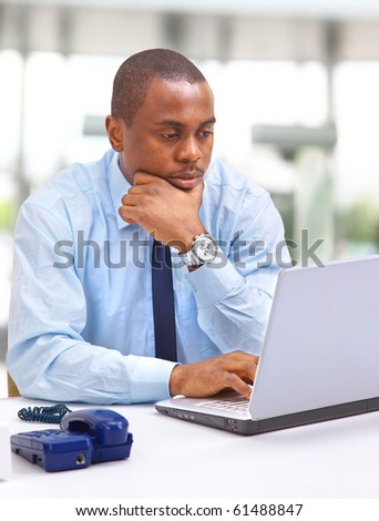 Portrait of a happy African American entrepreneur displaying computer laptop - stock photo