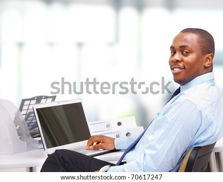 Portrait of a happy African American entrepreneur displaying computer laptop on white background - stock photo