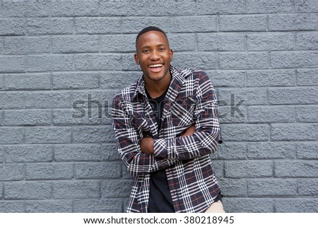 Portrait of a happy african american guy smiling with arms crossed - stock photo