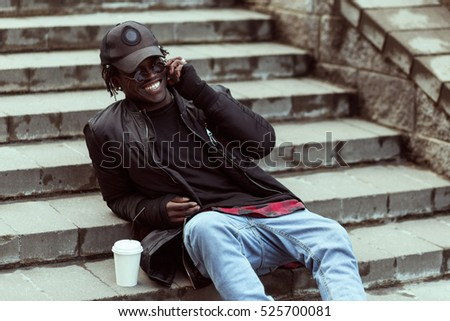 Portrait of a happy african american man sitting on stairs drinking cup of coffee with cell phone