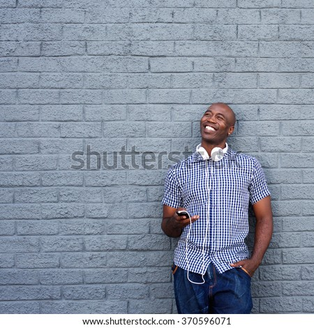 Portrait of a happy african american man standing against a gray wall with mobile phone and headphones  - stock photo