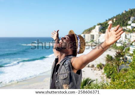 Portrait of a happy african american man with arms outstretched by the beach - stock photo