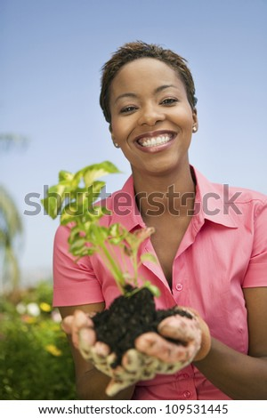 Portrait of a happy African American woman holding a plant - stock photo