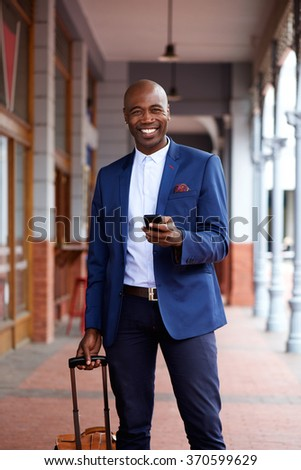 Portrait of a happy african businessman traveling with bag and mobile phone in city - stock photo