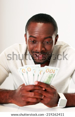 Portrait of a happy african man holding US dollars  - stock photo