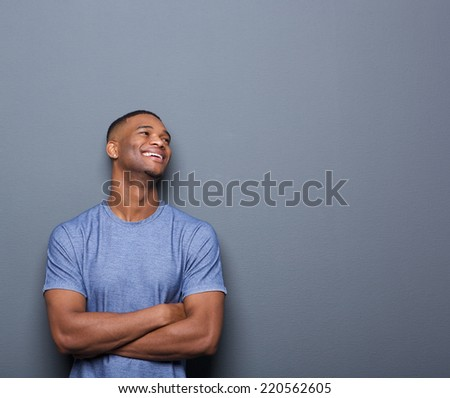 Portrait of a happy african man laughing with arms crossed on gray background - stock photo