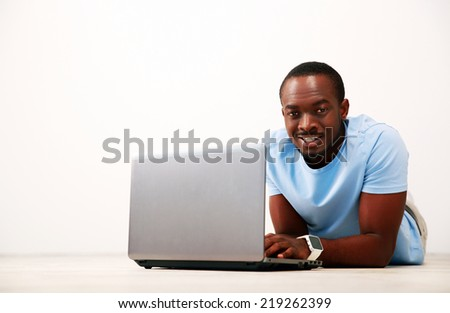 Portrait of a happy african man lying on the floor with laptop - stock photo