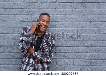 Portrait of a happy african man using mobile phone and smiling against gray wall - stock photo