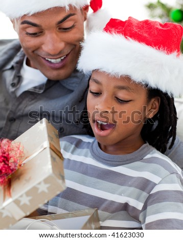 Portrait of a happy Afro-American father and son opening a Christmas gift - stock photo