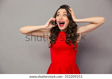 Portrait of a happy amazed woman in red dress talking on the phone over gray background - stock photo