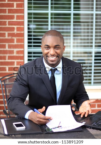 Portrait of a Happy and Attractive Young Professional African American Businessman Working On Paperwork - stock photo