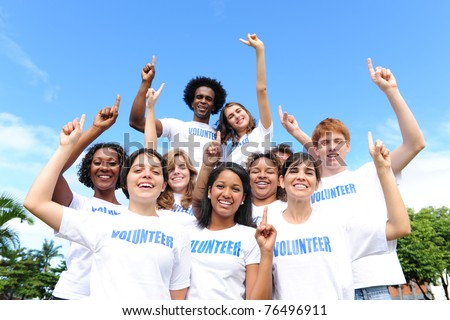 portrait of a happy and diverse volunteer group hands raised - stock photo