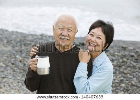 Portrait of a happy and loving mature couple at the beach - stock photo