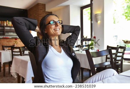 Portrait of a happy and pretty young woman sitting in a restaurant - perhaps she is the owner and just enjoys her break from work. - stock photo