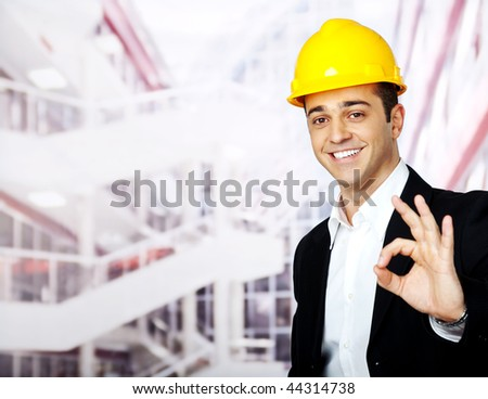 portrait of a happy architect with helmet, showing OK sign