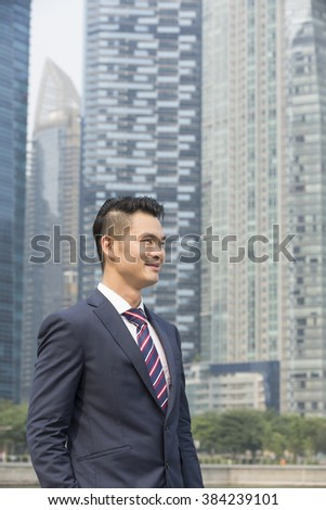Portrait of a happy Asian businessman looking away. Chinese business man standing outdoors. - stock photo