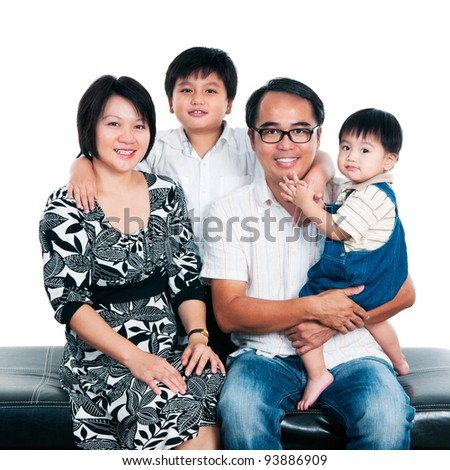 Portrait of a happy Asian family sitting together against white background. - stock photo