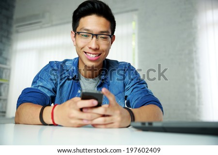 Portrait of a happy asian man sitting at the table with smartphone - stock photo