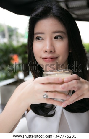 Portrait of a happy asian woman drinking coffee - stock photo