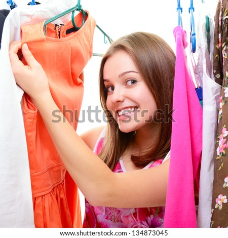 Portrait of a happy attractive teen girl making choices in wardrobe or in shop with clothes - stock photo