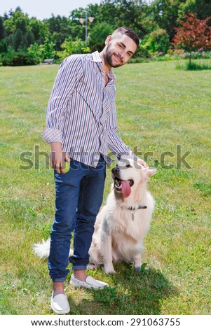 Portrait of a happy bearded man standing holding a tennis ball in one hand smiling, and stroking a head of his cute golden retriever sitting next to him in the grass in the park