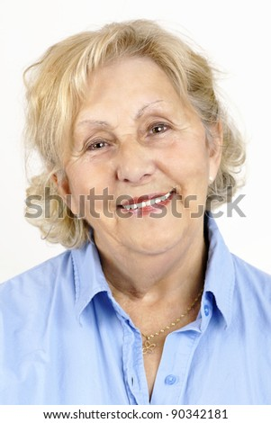 Portrait of a happy, beautiful and healthy senior woman wearing a blue shirt, isolated on white. - stock photo