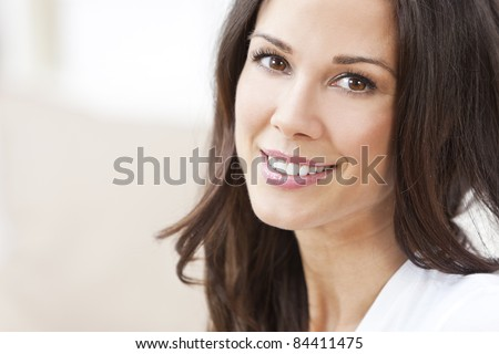 Portrait of a happy beautiful brunette young woman with perfect teeth & smile - stock photo