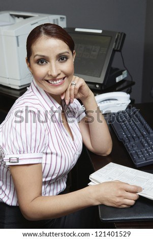 Portrait of a happy beautiful businesswoman sitting at desk - stock photo