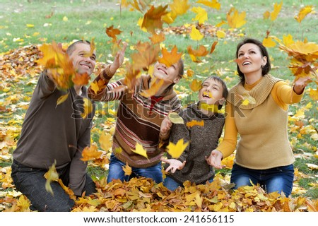 Portrait of a happy beautiful family throw autumn leaves - stock photo