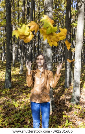 Portrait of a happy beautiful teenage girl enjoying the autumn season in the forest - stock photo
