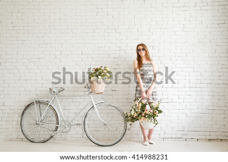 Portrait of a happy beautiful young girl with vintage bicycle and flowers - stock photo