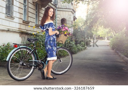 Portrait of a happy beautiful young girl with vintage bicycle and flowers on city background in the sunlight outdoor. Cruiser with basket full of flowers. Active Leisure Concept.  - stock photo