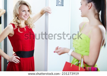 Portrait of a happy blond girl talking to her friend in clothing department - stock photo