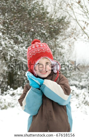 Portrait of a happy boy outdoors in the snow. - stock photo