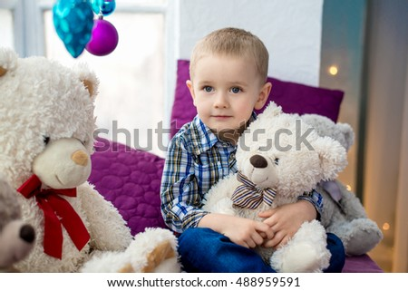 Portrait of a happy boy 3-4 years, holding a white teddy bear
