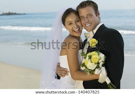 Portrait of a happy bride and groom embracing on the beach - stock photo