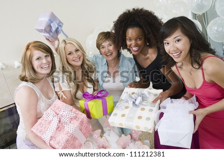 Portrait of a happy bride with her friends and mother at party - stock photo