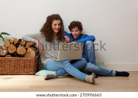 Portrait of a happy brother and sister sitting on floor at home using laptop together - stock photo