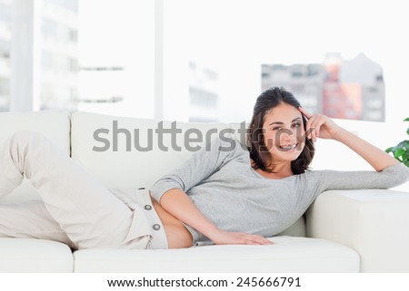Portrait of a happy brunette on her sofa in a bright living room