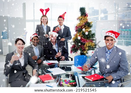 Portrait of a happy business team toasting with Champagne at a Christmas party against snow falling - stock photo