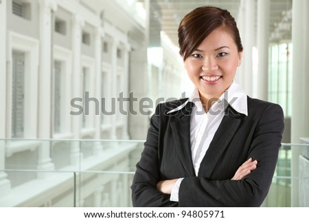 Portrait of a happy business woman standing with folded arms. - stock photo