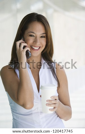Portrait of a happy business woman using cell phone with disposable glass in office break