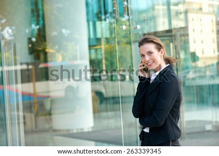 Portrait of a happy business woman walking and calling by mobile phone outside - stock photo