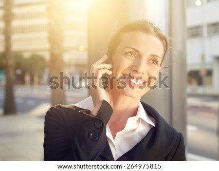 Portrait of a happy business woman walking and talking on mobile phone outside - stock photo