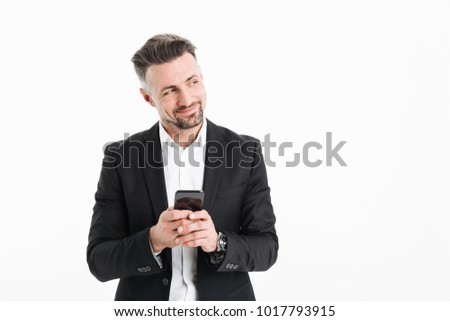 Portrait of a happy businessman dressed in suit holding mobile phone and looking away at copy space isolated over white background