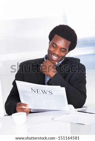 Portrait Of A Happy Businessman Reading Newspaper - stock photo