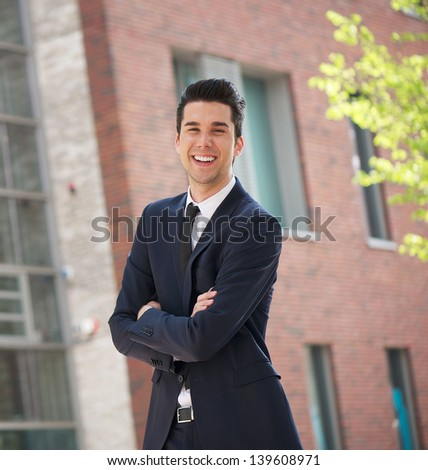 Portrait of a happy businessman relaxing outdoors with arms crossed - stock photo