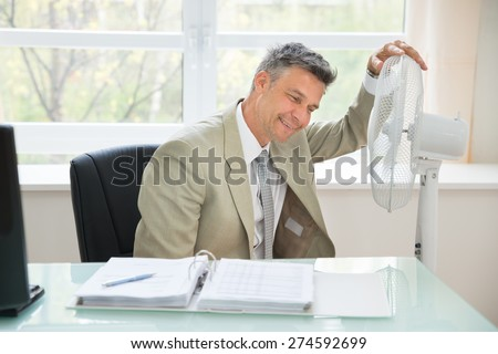 Portrait Of A Happy Businessman Sitting Near Fan In Office - stock photo