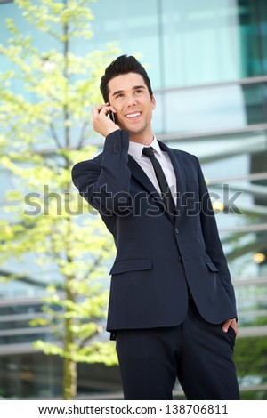Portrait of a happy businessman talking on mobile phone outdoors - stock photo