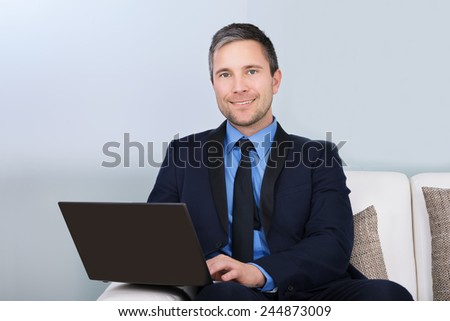 Portrait Of A Happy Businessman Using Laptop Sitting On Couch - stock photo